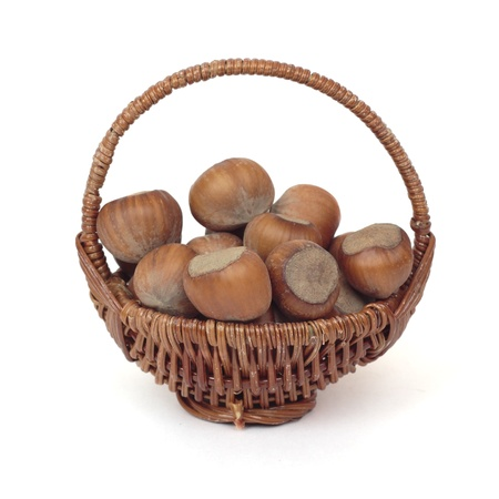 full willow: Wicker basket with hazelnuts isolated on a white background Stock Photo