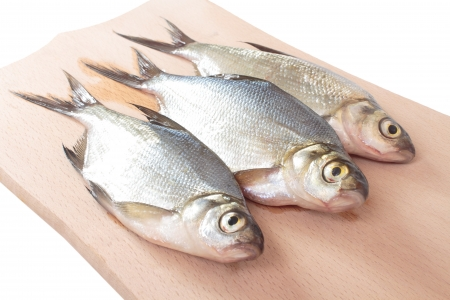 Fish fry on a wooden board  Isolated on white photo