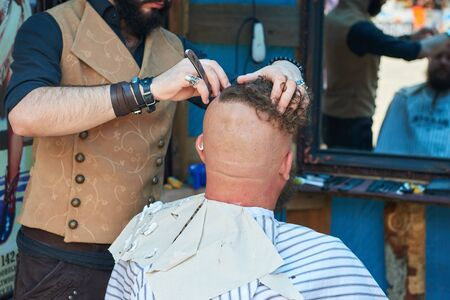 barbershop: CHERNIVTSI, UKRAINE - JULY 22, 2017: Stylish hairdresser in the cylinder cap Shears and shaves a biker with red hair at the festival Moto-picnic Retrodrom 2017