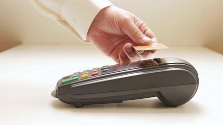 Pago en comercio con sistema nfc y tarjeta sin contacto. Foto de archivo