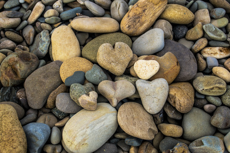 river rocks: A pile of rock shaped hearts on the beach with other river rocks Stock Photo