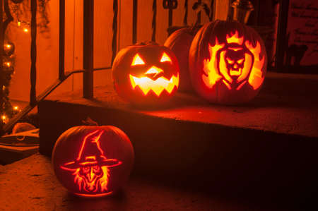 3 carved pumpkins sit on the steps of a home on the night of halloween