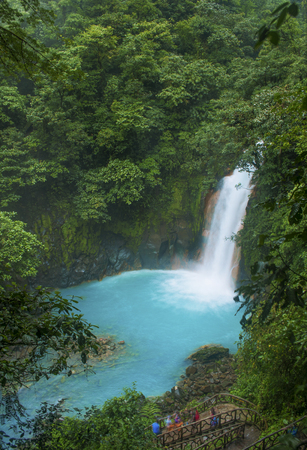 A view of rio celeste waterfall with some onlookers.