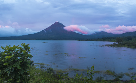 The changing colors of the clouds during a sunset on Arenal Volcano