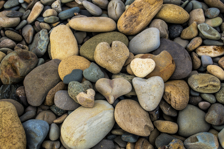 A pile of rock shaped hearts on the beach with other river rocks Reklamní fotografie