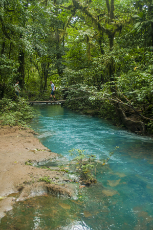 Kids walk across a bridge at Rio Celeste in Costa Rica