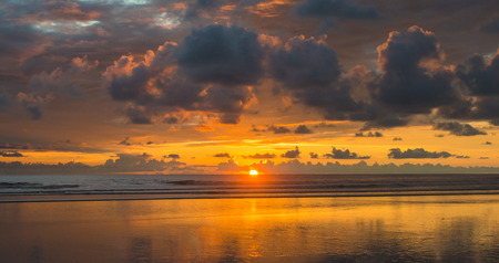 A beautiful cloudy sunset over the pacific ocean at Domnical beach in the southern part of Costa Rica.