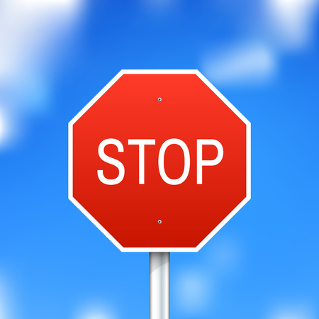 Red stop sign on blue sky background