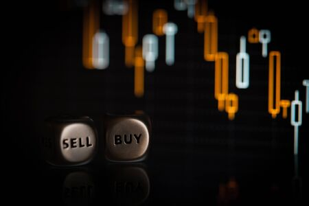 Sell and buy dice on blurred candlestick chart. Close-up stock photo Stockfoto