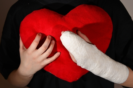 Hand in plaster and red heart