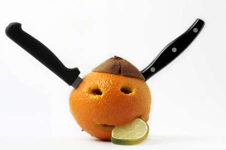 an orange face with lemon and knives