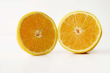 An entire and two half oranges put together on a white table