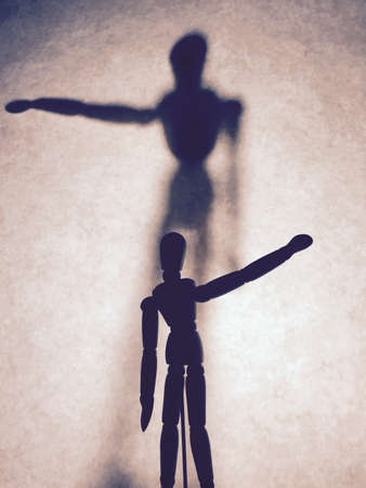 wood figurine: Concept of select. Wooden figurine and shadow Stock Photo