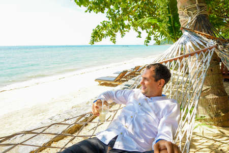 シービューのハンモックでリラックス シャツ カクテルで若い男は。オフィス ワーカーの休暇 写真素材