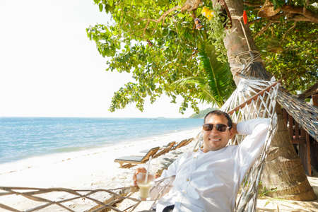 Young man with cocktail in shirt relaxing in hammock with sea view. Office worker's vacation