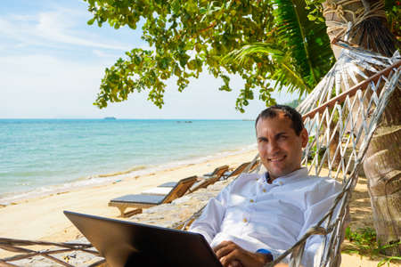 Young man work on laptop in white shirt relaxing in hammock with seaview
