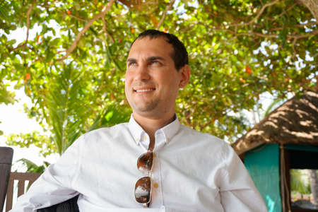 Portrait of dreaming young caucasian man in white shirt in tropical surroundings