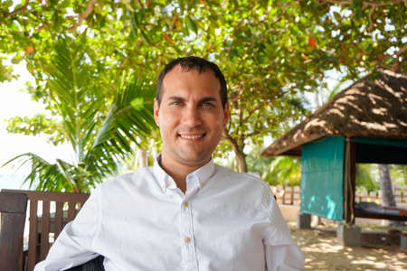 Portrait of happy young caucasian man in white shirt in tropical surroundings Banco de Imagens