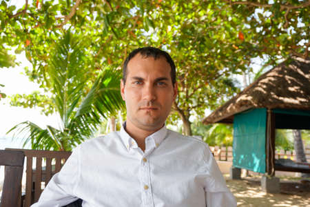Portrait of serious young caucasian man in white shirt in tropical surroundings