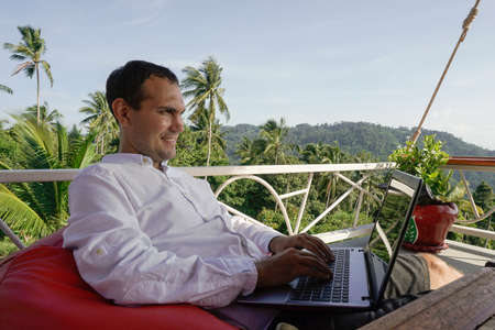 Young man work on laptop relaxing on tropical terrace. Remote workplace