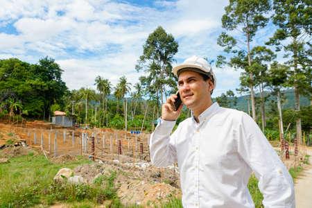 真剣に建設現場で携帯電話で話しているエンジニア 写真素材