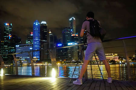 Man taking photo of night skyscrapers in Singapore Editorial