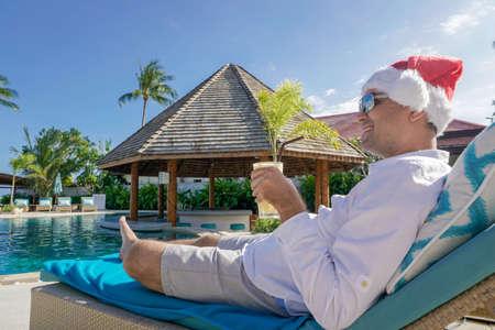 サンタ クロースの帽子でくつろぐソニー a6300 で撮影したプールの男