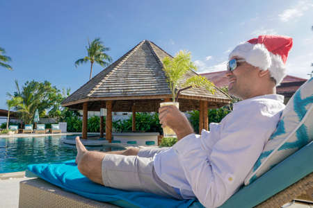 Man in Santa Claus Hat Relaxes by the Pool shot with a Sony a6300 Banco de Imagens