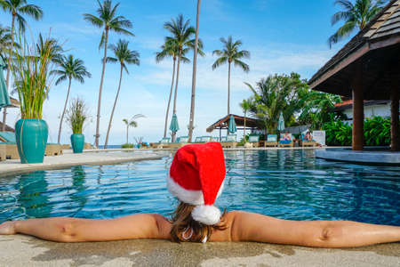 Woman in Santa Claus Hat Relaxes in the Pool shot with a Sony a6300