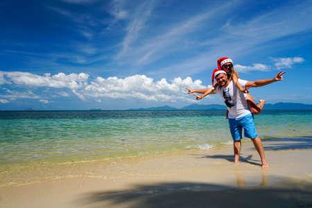 ロマンチックなカップルはサンタ クロースの帽子とビーチで楽しい時を過す