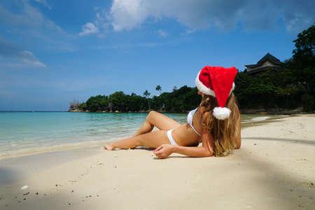 Woman on the Beach with Santa Claus Hat Banco de Imagens