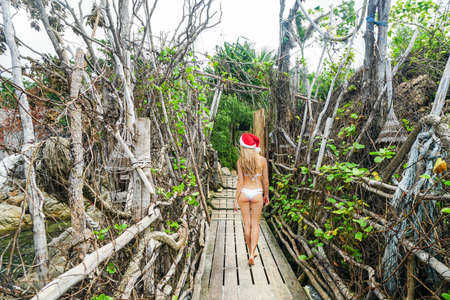 サンタ クロースの帽子の若い女性が本格的な木造橋を渡って歩いてください。 写真素材