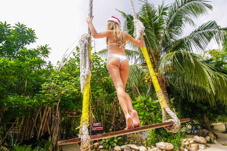 Young Woman in Santa Claus Hat on Swings