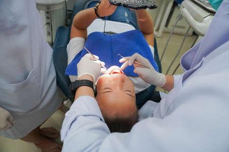 女性は歯科クリニックで歯を修正します。