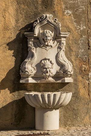 Stucco molding on the fountain against a wall in Cascais, Portugal photo