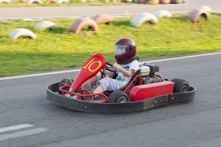 The child goes on a straight line on a go-cart to carting club  Editorial