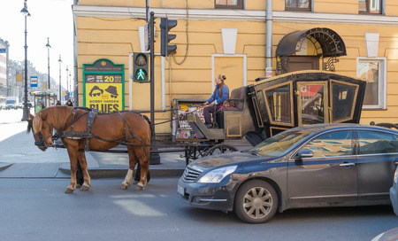 The car and horse crew with the carriage stand on the traffic light in St  Petersburg