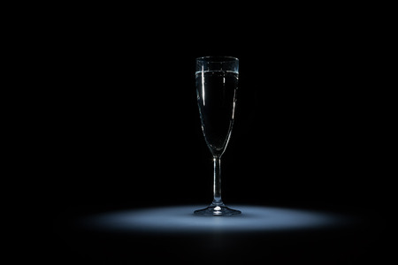 compensatory: Elegant glass of water with bubbles on the black background on light spot