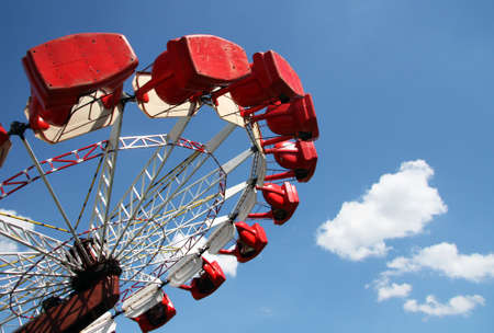 Carousel on blue sky with white clouds photo