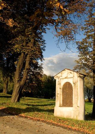 sacramentale: Cappella e albero in autunno, con nuvole e cielo blu