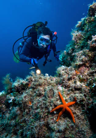 vastness: Scuba diver with red starfish in front  Stock Photo
