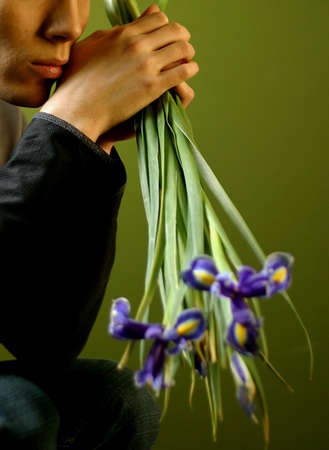 Young the man with a bouquet of irises in hands photo