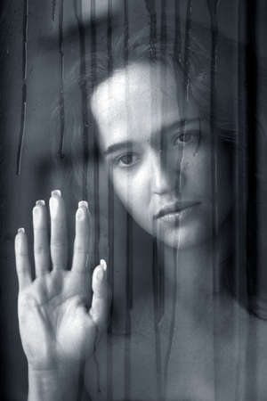 woman behind a wet window. bw photo