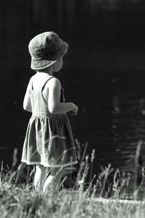 The girl sits on a coast of lake Stock Photo