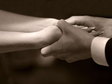 agrees: Female hands in mans hands on a dark background. bw+sepia