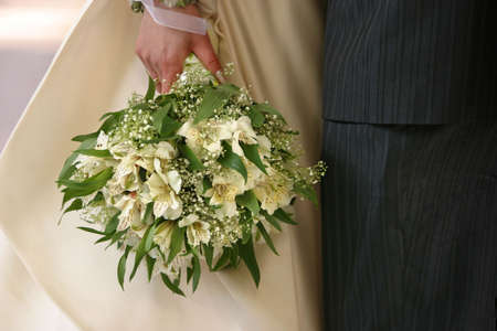 Bouquet of flowers on a background of a dress of the bride and a suit the groom Stock Photo - 542480