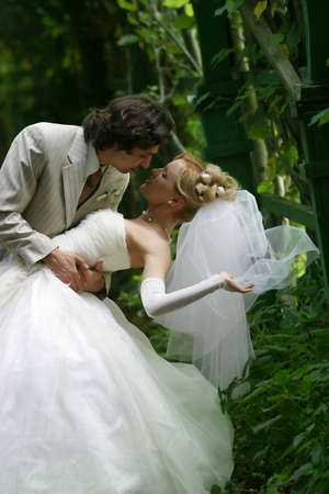 The groom and the bride kissed in park