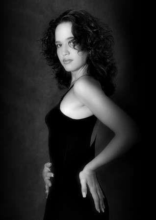 Portrait of the harmonous girl in a black dress on a dark background. b/w Stock Photo - 548843