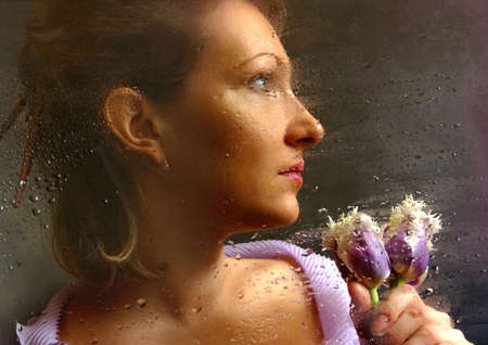 The woman with tulips behind of a damp window photo