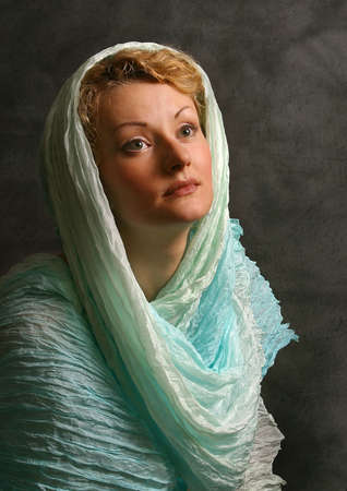 The beautiful girl in a blue scarf in studio photo